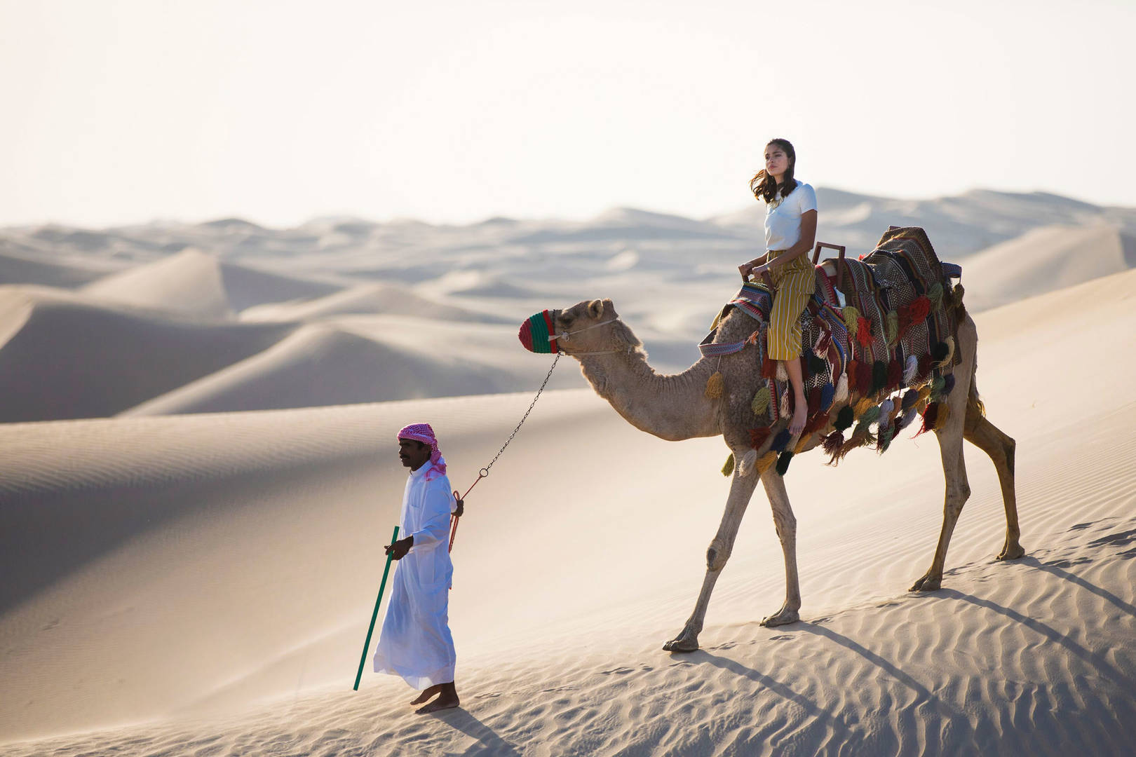 Lady riding a camel in the desert