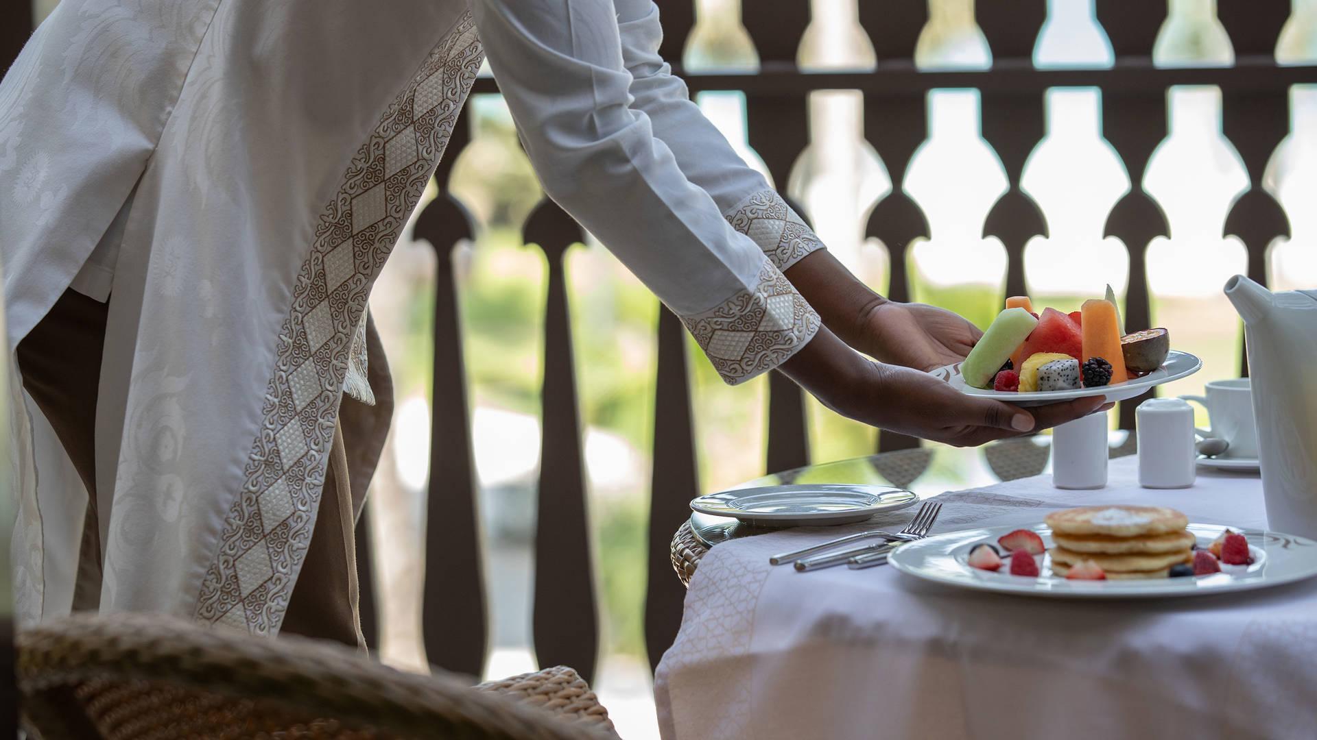 Frau serviert Frühstück im Hotel Jumeirah Dar Al Masyaf