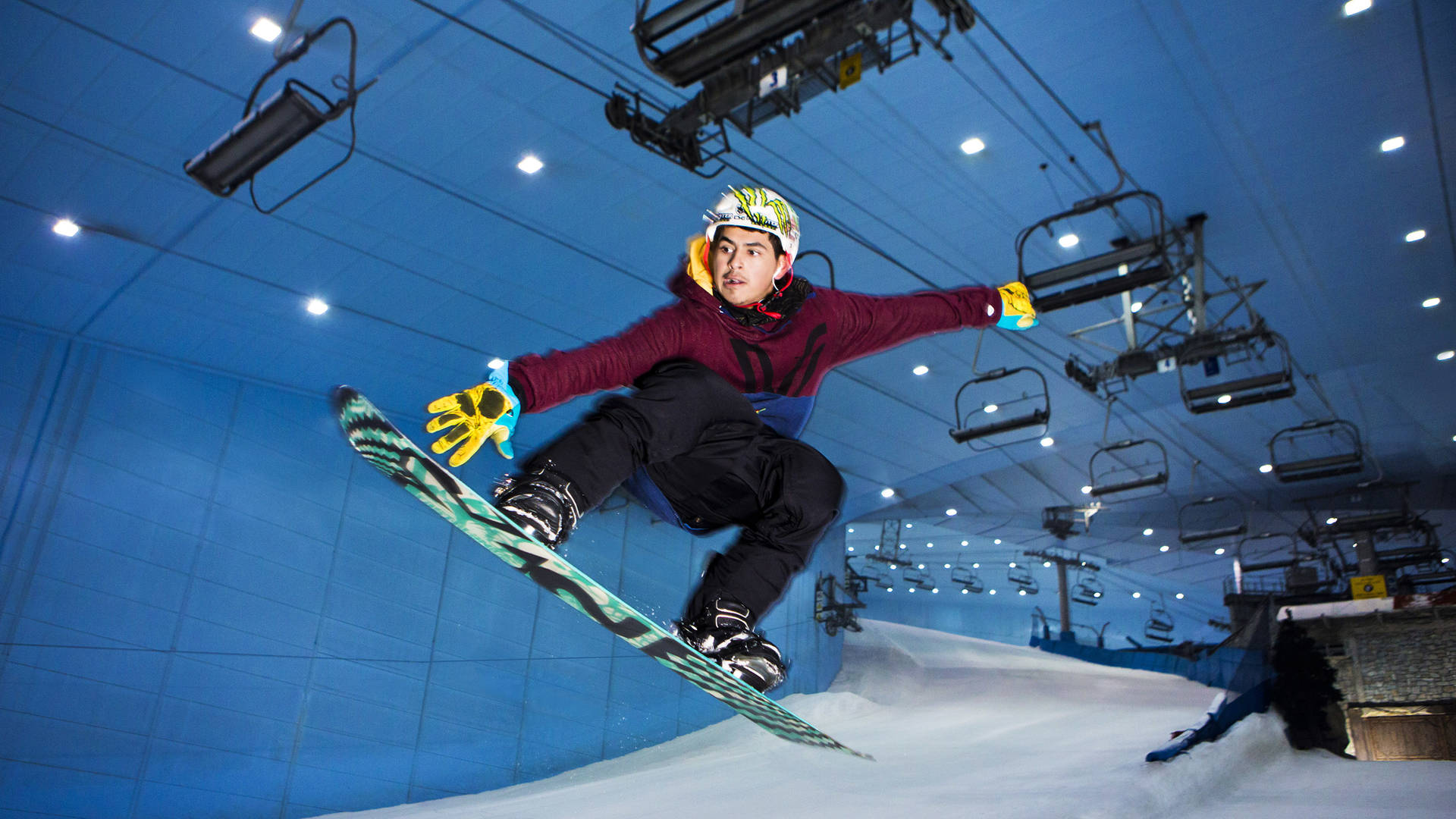 A young boy snowboard's down Ski Dubai's slope