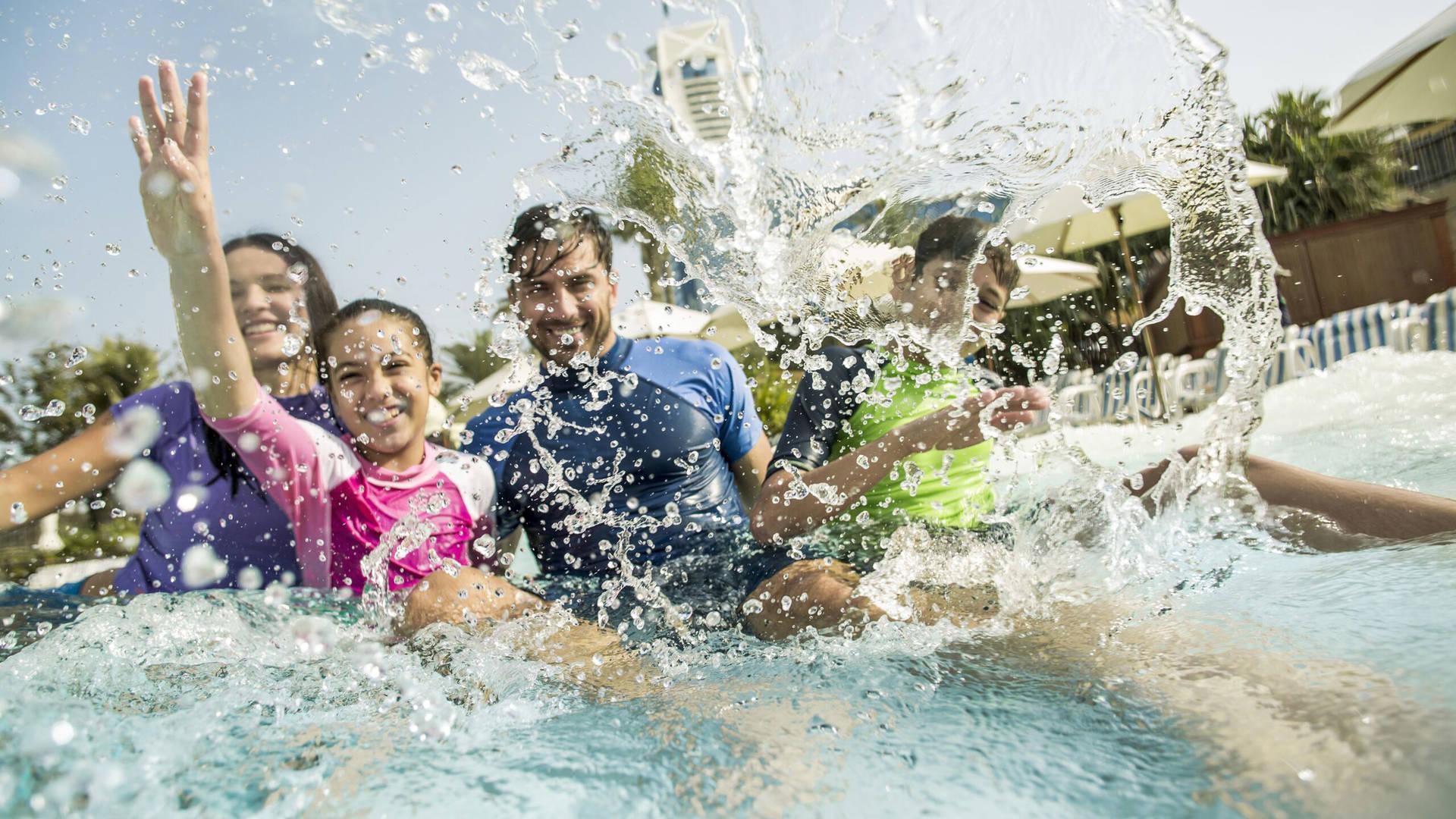 A family splashing in the Wild Wadi slide