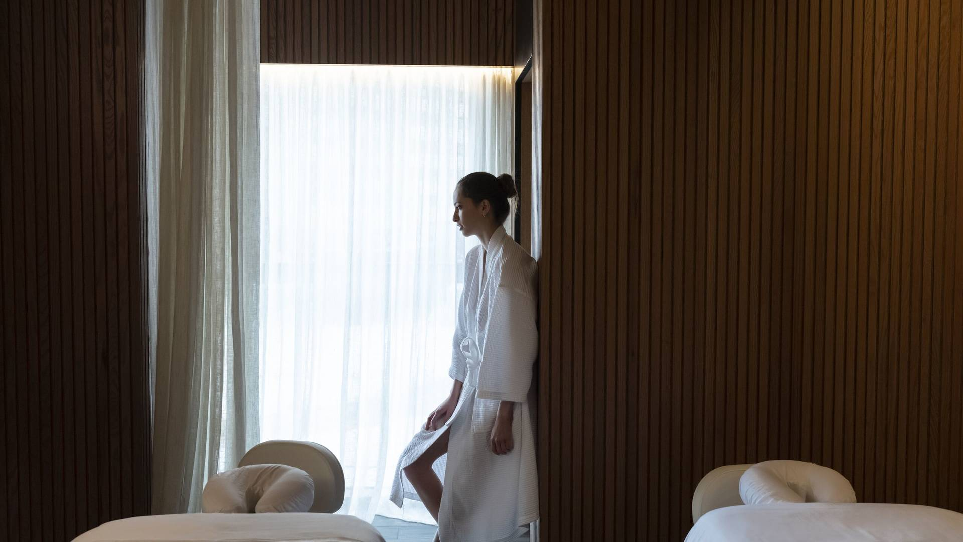 Lady standing by a curtain at Jumeirah Zabeel House Native Club Spa at The Greens