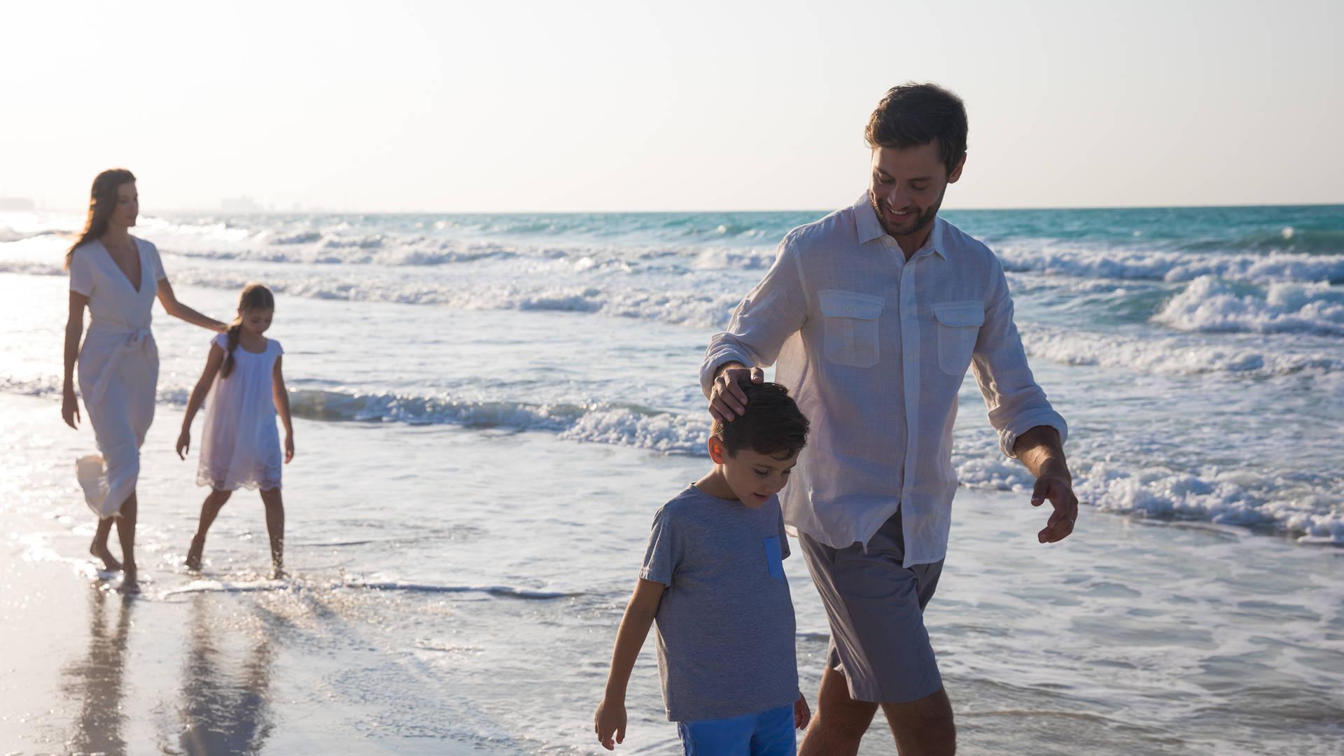 Family walking along the shore at Jumeirah Saadiyat Island Resort