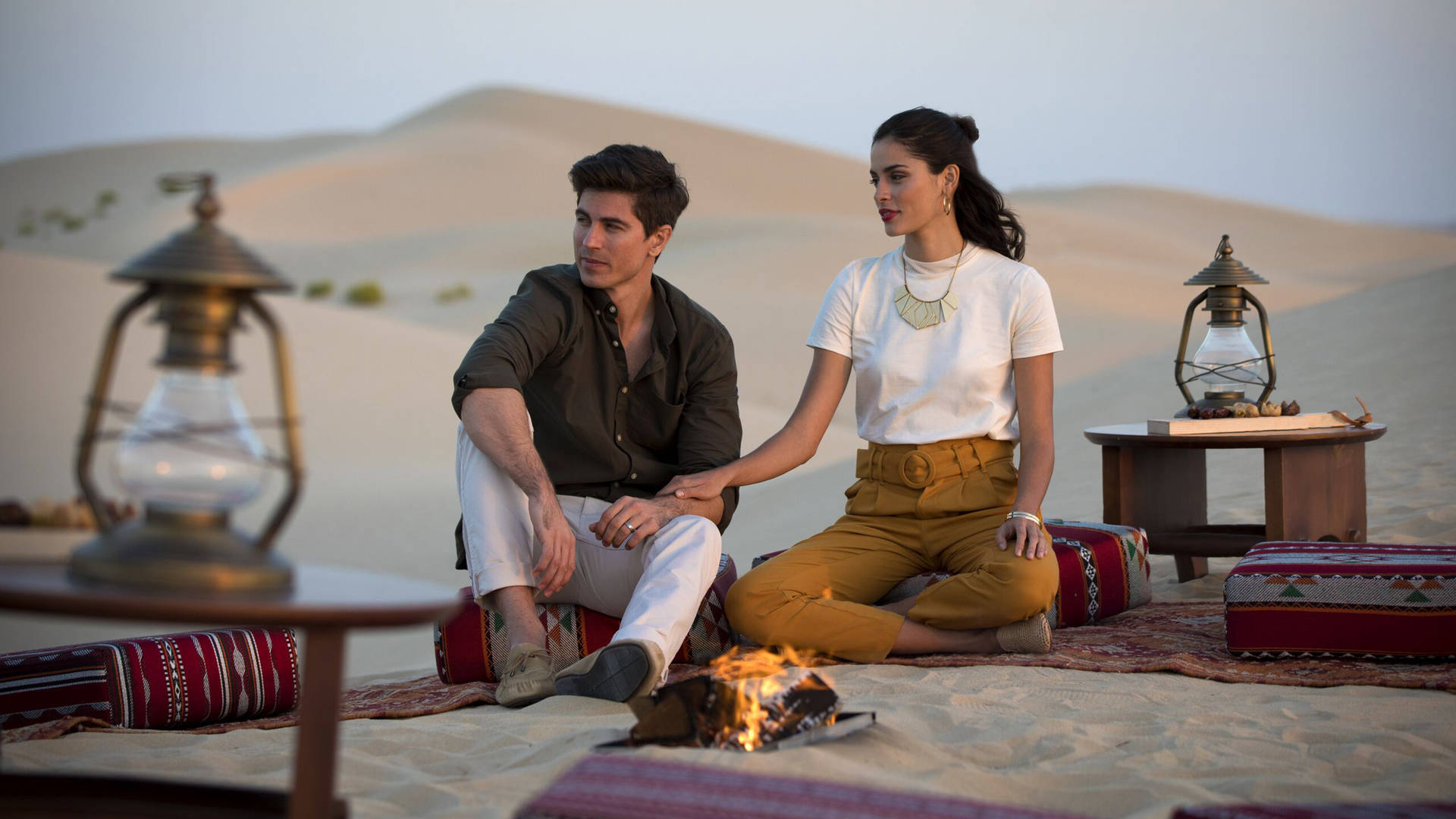 Couple sitting on Bedouin cushions in the desert