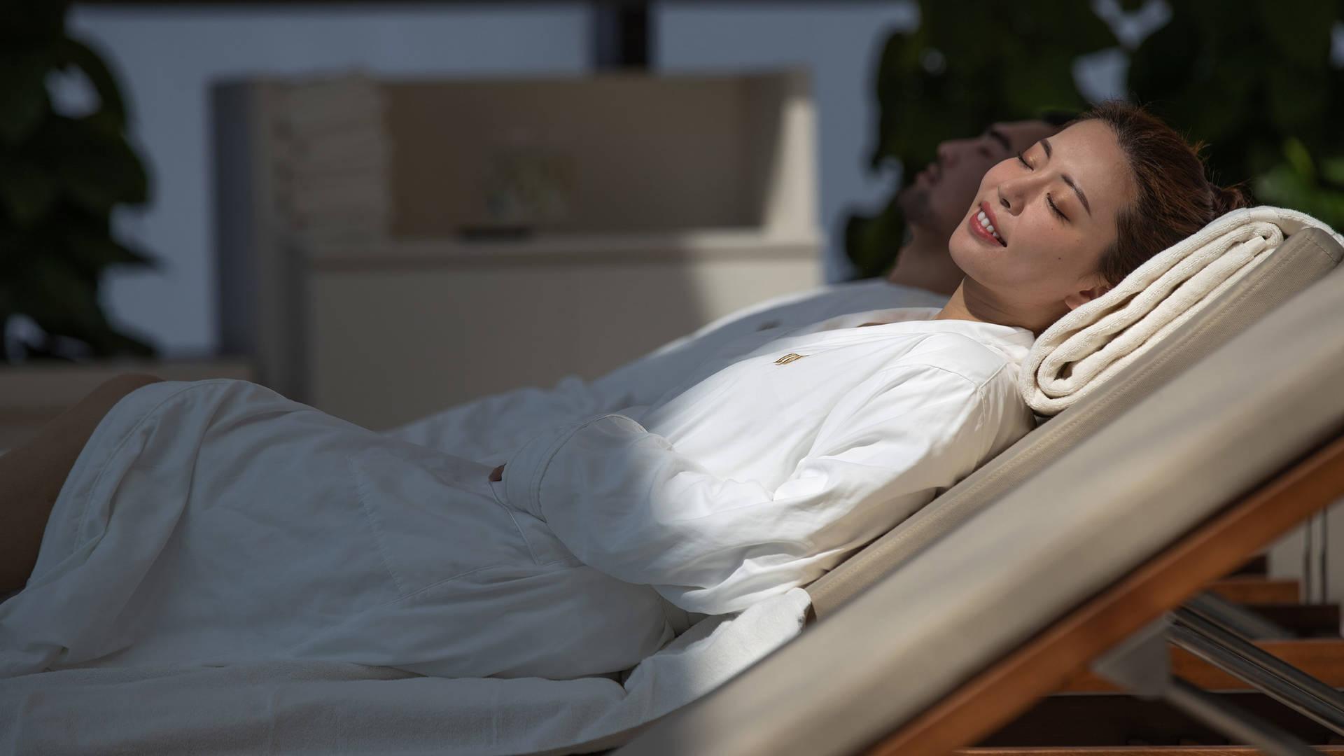 Jumeirah Nanjing couple relaxing on sun bed_16-9