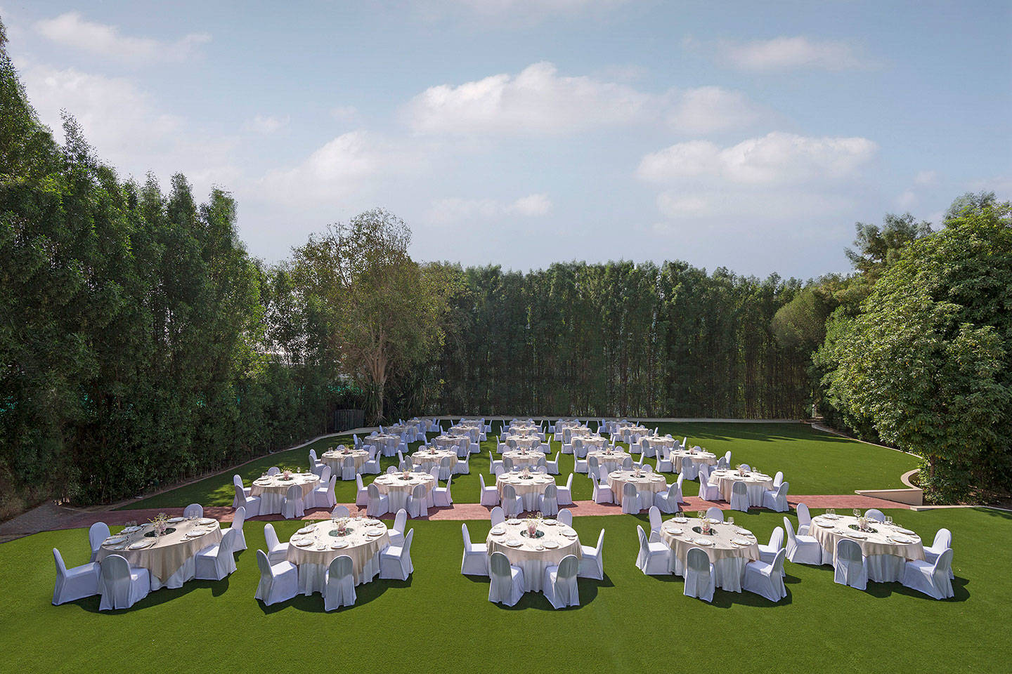 Tables set up on lawn for event at Jumeirah Creekside Hotel