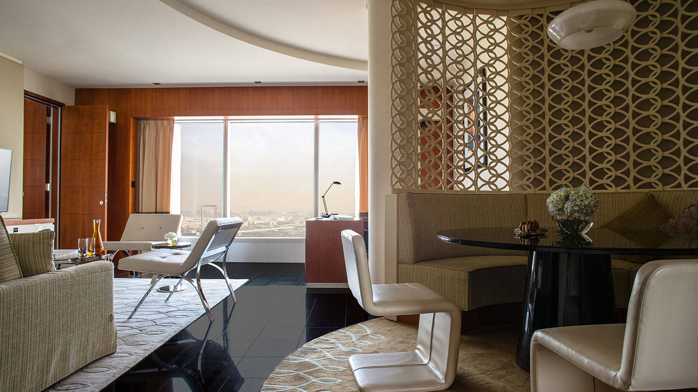 Jumeirah Emirates Towers living area of suite with dining table and lounge