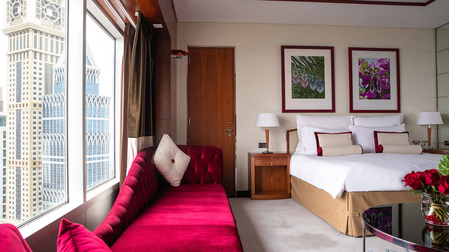 Jumeirah Emirates Tower luxurious red divan and bed overlooking vast view