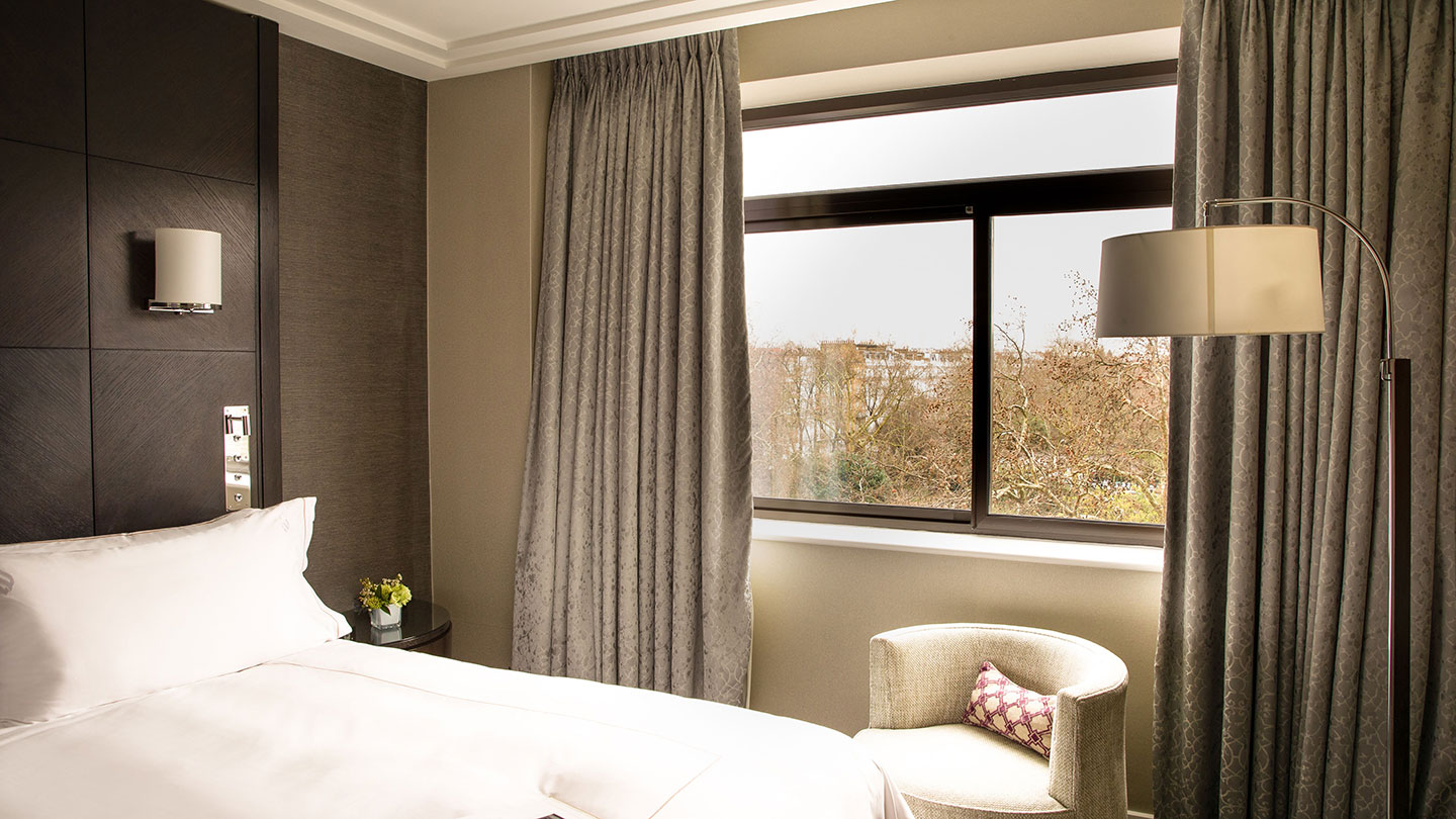 Bedroom with view of garden at Jumeirah Carlton Tower