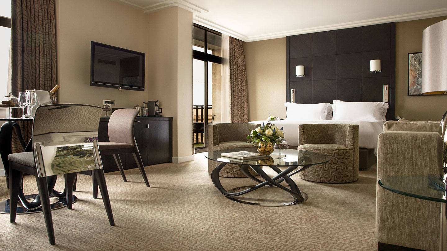 View of luxurious bed and living area of a suite at Jumeriah Carlton Tower
