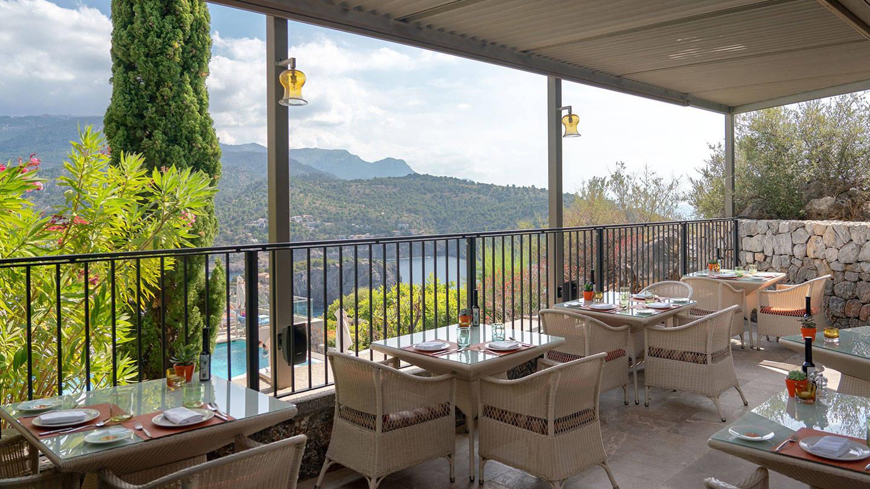 Terrasse von Es Fanals mit Tischen und Bergblick